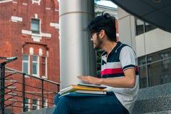 Junger Student sitzt auf einer Straße mit Büchern und blickt in Richtung Lizenzfreie Stockbilder