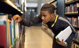 Junger Student, welche nach Büchern an der Bibliothek sucht Stockfotografie