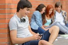Junger Studentenmann, der heraus mit Freunden hängt Stockfotografie