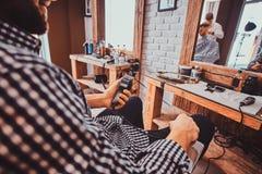 Junger styilish Mann im karierten Hemd sitzt am besch?ftigten Friseursalon und h?lt Trimmer f?r Haarschnitt stockfoto