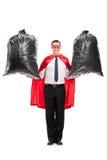 Junger Superheld, der zwei Abfalltaschen hält Stockbilder