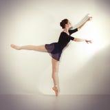 Junger Tänzer, der in einem Studio aufwirft stockfotografie