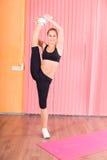 Junger Tänzer-Holding Leg Above-Kopf im rosa Studio Stockfoto