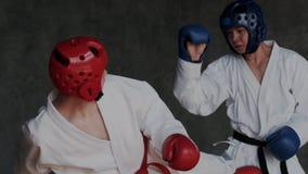 Junger talentierter Kerl, der seinen Rivalen in den Mischungskampfkünsten angreift Jungen in geschütztem Sturzhelm mit Handschuhe stock footage