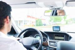 Junger Taxifahrer, der sein Auto fährt Stockfotografie