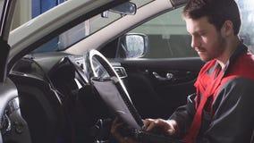 Junger Technikermann, der Maschinenservice vom Auto in der Garage macht stock video footage