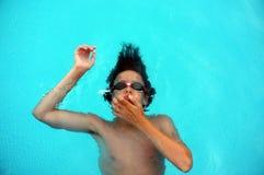 Junger Teenager, der auf Wasser legt Stockbild
