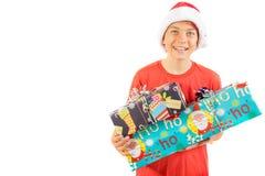 Junger Teenager, der einen Santa Christmas-Hut mit einem Geschenk trägt Stockbild