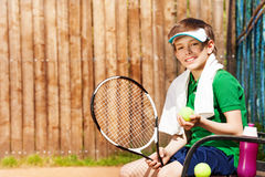 Junger Tennisspieler, der auf einer Bank nach Spiel sitzt Stockbilder