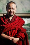 junger tibetanischer buddhistischer Mönch in einem roten Kleid vor seinem Klostertempel lizenzfreies stockbild