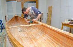 Junger Tischler, der neues Kanu in der Werkstatt versandet Lizenzfreie Stockfotos