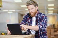 Junger Tischler des Porträts, der Laptop verwendet stockfoto