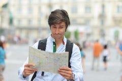 Junger Tourist, der die Karte aufpasst Lizenzfreie Stockfotografie