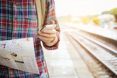 Junger Tourist mit dem Bart, der eine Karte hält und Handy verwendet Stockfotos