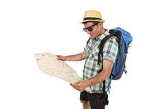 Junger touristischer schauender Mannlesestadtplan entspannter und glücklicher tragender tragender Sommerhut des Rucksacks Lizenzfreie Stockfotos