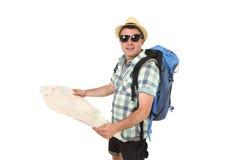 Junger touristischer schauender Mannlesestadtplan entspannter und glücklicher tragender tragender Sommerhut des Rucksacks Stockfoto