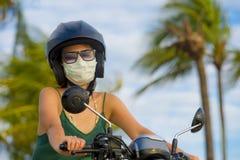 Junger tragender Motorradsturzhelm des glücklichen und recht asiatischen Chinesinreitrollers und schützende Gesichtsmaske im Moto lizenzfreie stockbilder