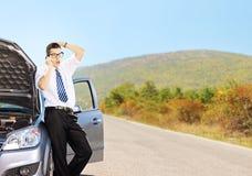Junger trauriger Mann auf einem defekten Auto sprechend an einem Handy lizenzfreies stockbild