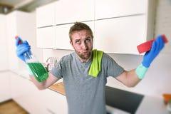 Junger trauriger Mann in den Gummihandschuhen, die mit Reinigungsmittel Hauptspülbecken abbrausend und machend säubern Stockbild