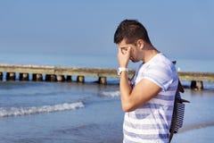 Junger trauriger Mann, der allein auf dem Strand steht Stockfotos