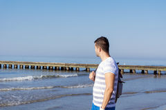 Junger trauriger Mann, der allein auf dem Strand steht Lizenzfreies Stockfoto