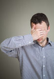 Junger trauriger Mann, der sein Gesicht mit der Hand versteckt Stockbilder
