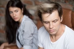 Junger trauriger Mann, der an Verrat, umgekippte Freundin am backgrou denkt Stockfotografie