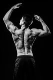 Junger und geeigneter Bodybuilderathlet demonstriert hintere Ansicht des Bizepses über schwarzen Hintergrund Lizenzfreie Stockbilder