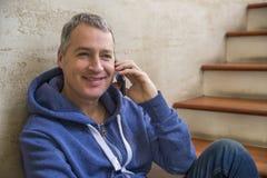 Junger und gesunder Mann, der zu Hause am intelligenten Telefon lächelt und spricht Lizenzfreie Stockfotos