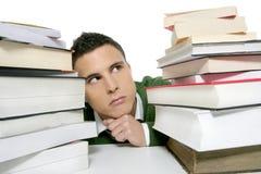 Junger unglücklicher Kursteilnehmer mit gestapelten Büchern stockfotografie