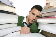 Junger unglücklicher Kursteilnehmer mit gestapelten Büchern Stockbild