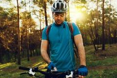 Junger unrasierter europäischer Radfahrer im Sturzhelm, tragendes blaues Radfahrent-shirt, Handschuhschaltverzögerungsmodus auf s stockfotografie