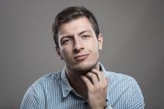 Junger unrasierter Mann, der juckenden Bart mit schmerzlichem Ausdruck verkratzt lizenzfreie stockfotografie