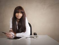 Junger Unternehmensleiter, der am Schreibtisch mit digitaler Tablette arbeitet Stockfotos