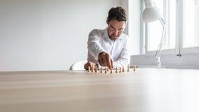Junger Unternehmensleiter, der weiße Schachfiguren in einer vernünftigen Struktur in Position bringt stockbild