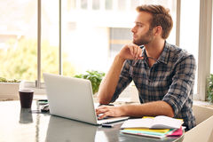 Junger Unternehmer, der heraus das Fenster im Gedanken schaut Lizenzfreie Stockfotografie
