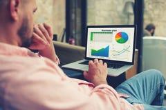 Junger Unternehmer, der Leistung auf seinem Notizbuch analysiert Stockbilder