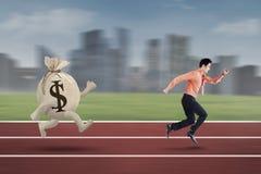 Junger Unternehmer gejagt durch Tasche des Dollars Lizenzfreies Stockfoto