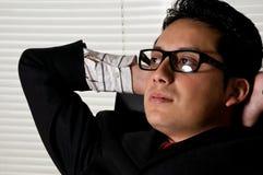 junger Unternehmermann, der im Büro sich entspannt Stockbilder
