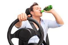 Junger unverantwortlicher Mann, der ein Bier fährt und trinkt Stockfoto