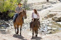 Junger Vater als Pferdelehrer der Tochter des jungen jugendlich, die tragenden Cowgirlhut des kleinen Ponys reitet stockbild