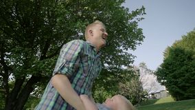 Junger Vater, der auf Händen sein kleines Kind nimmt und oben seins an der Wiese an einem sonnigen Tag in der Parkzeitlupe voll w stock footage