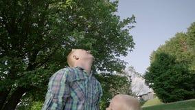 Junger Vater, der auf Händen sein kleines Kind nimmt und oben seins an der Wiese an einem sonnigen Tag in der Parkzeitlupe voll w stock video
