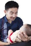 Junger Vater, der am Baby lächelt Lizenzfreies Stockbild