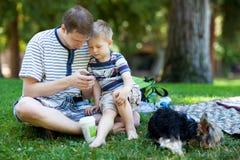 Junger Vater, der draußen zu seinem Sohn liest lizenzfreie stockbilder