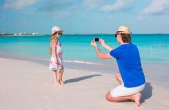Junger Vater, der Foto auf Mobiltelefon seines Kindes auf dem Strand macht Lizenzfreie Stockfotografie