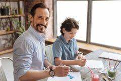 Junger Vater, der glücklich ist, mit seinem Sohn zu malen Lizenzfreies Stockbild