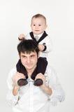 Junger Vater, der kleinen Sohn auf seinen Schultern anhält stockbild