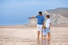 Junger Vater, der mit seiner Sohn- und Babytochter auf Strand spielt Lizenzfreie Stockbilder