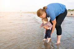 Junger Vater, der sein Kind über Meerwasser hält Stockbild